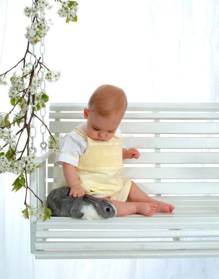 Bebé que acaricia el conejito fotos de archivo