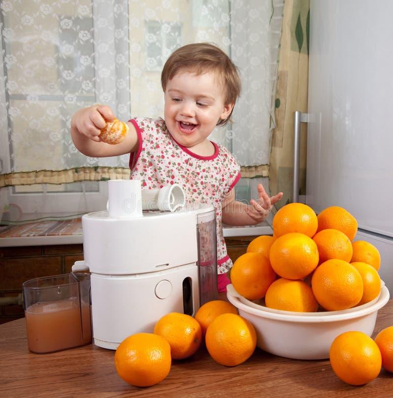 Bebé que adiciona a laranja ao juicer imagem de stock