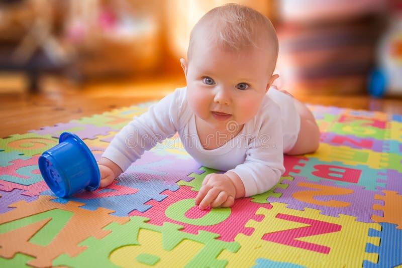 Bebé que alcanza la taza en la estera del alfabeto imagen de archivo libre de regalías