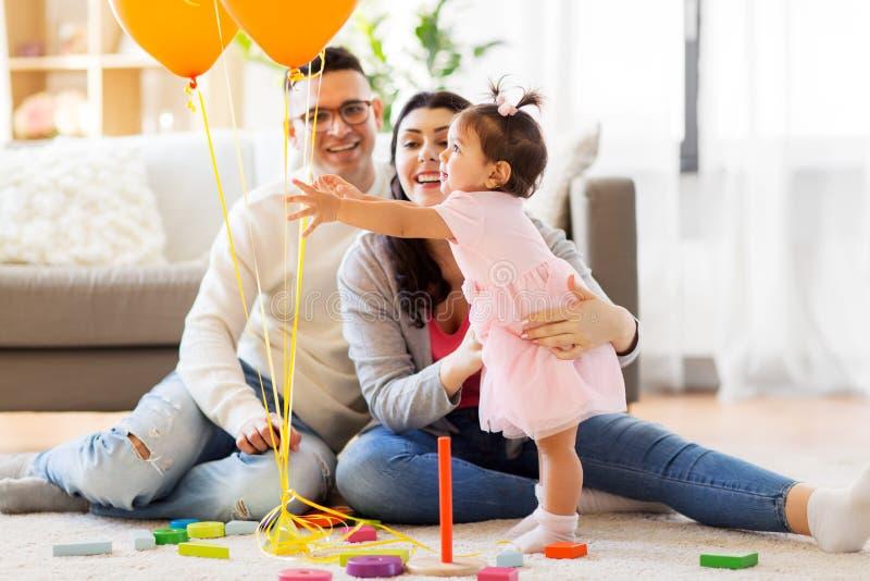 Bebé que alcanza a los globos en la fiesta de cumpleaños imagenes de archivo