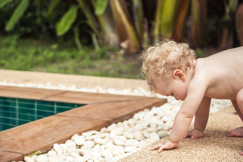 Bebé que aprende caminar haciendo esfuerzos para levantarse imagen de archivo