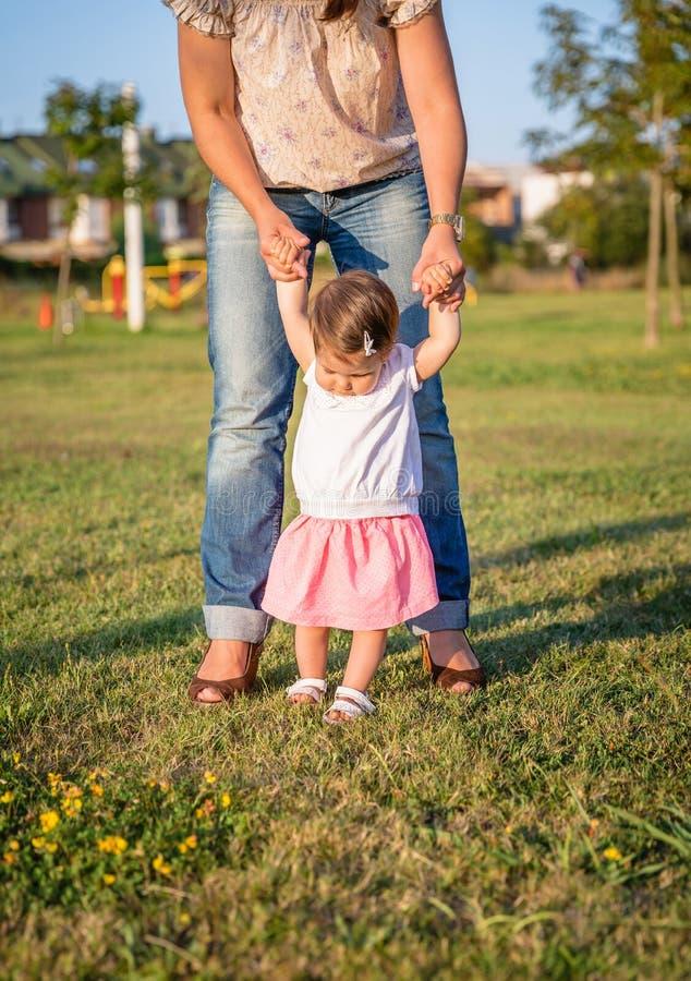 Bebé que aprende caminar sobre un parque de la hierba imagenes de archivo