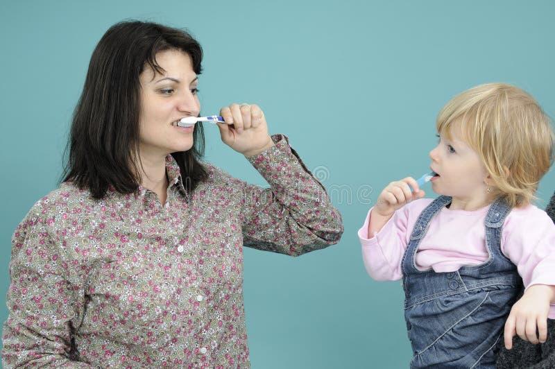 Bebé que aprende los dientes que aplican con brocha imagen de archivo