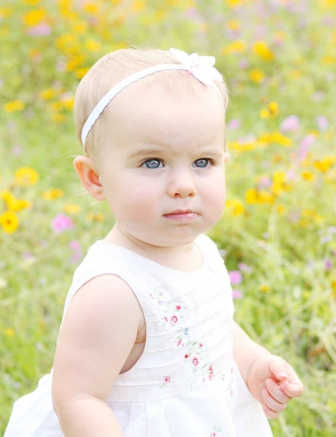 Bebé que camina en flores imagen de archivo