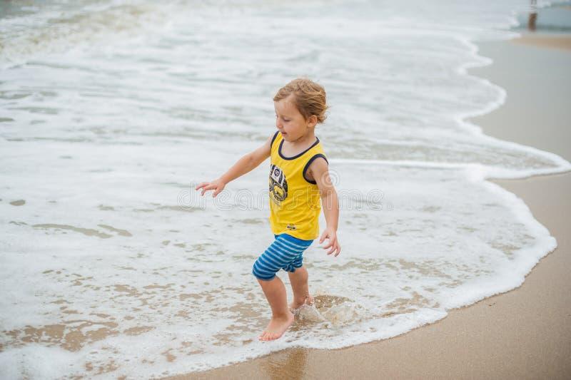 Bebé que camina en la playa arenosa cerca del mar Niño lindo en la playa tropical de la arena imagenes de archivo