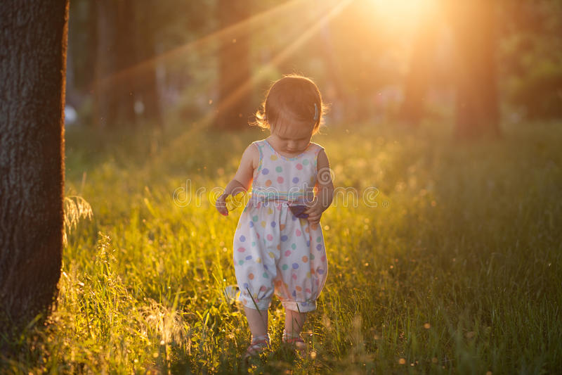 Bebé que camina en luces de la puesta del sol imagenes de archivo