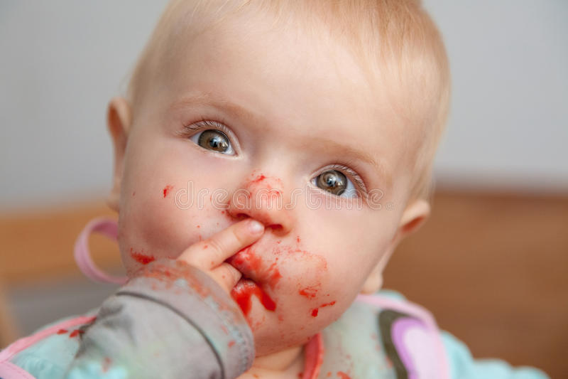 Bebé que come, face suja foto de stock