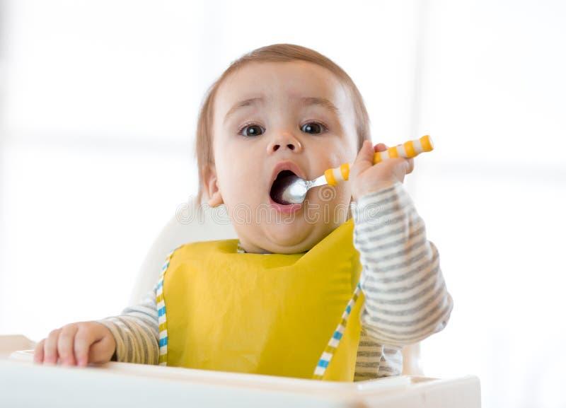 Bebé que come la comida sana con la mano izquierda en casa fotos de archivo