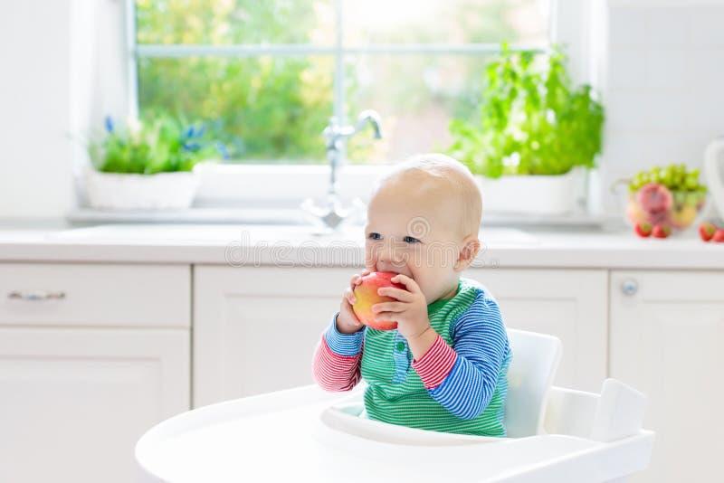 Bebé que come la manzana en la cocina blanca en casa imagen de archivo