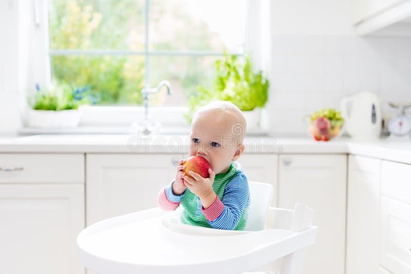 Bebé que come la manzana en la cocina blanca en casa imagen de archivo libre de regalías