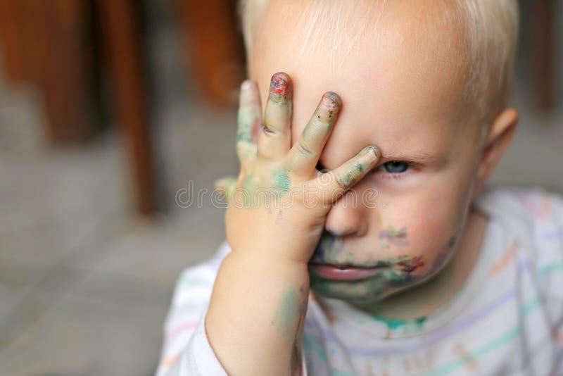 Bebé que cubre la cara sucia con las pequeñas manos imágenes de archivo libres de regalías