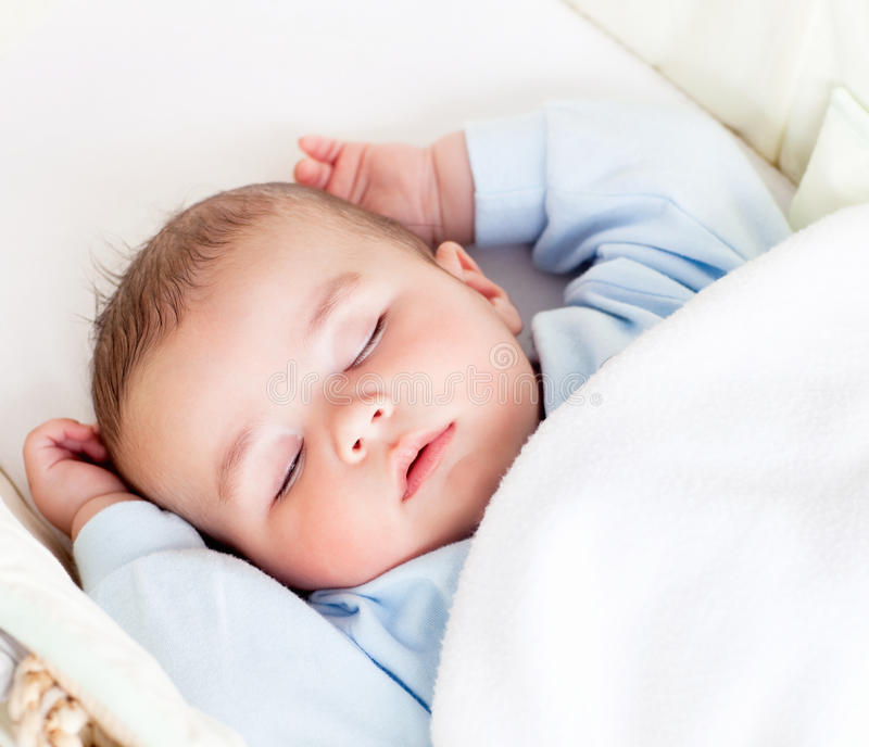 Bebé que dorme pacificamente em seu berço fotografia de stock