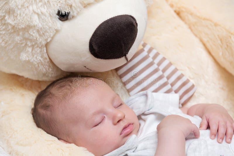 Bebé que duerme con Teddy Bear grande fotografía de archivo libre de regalías