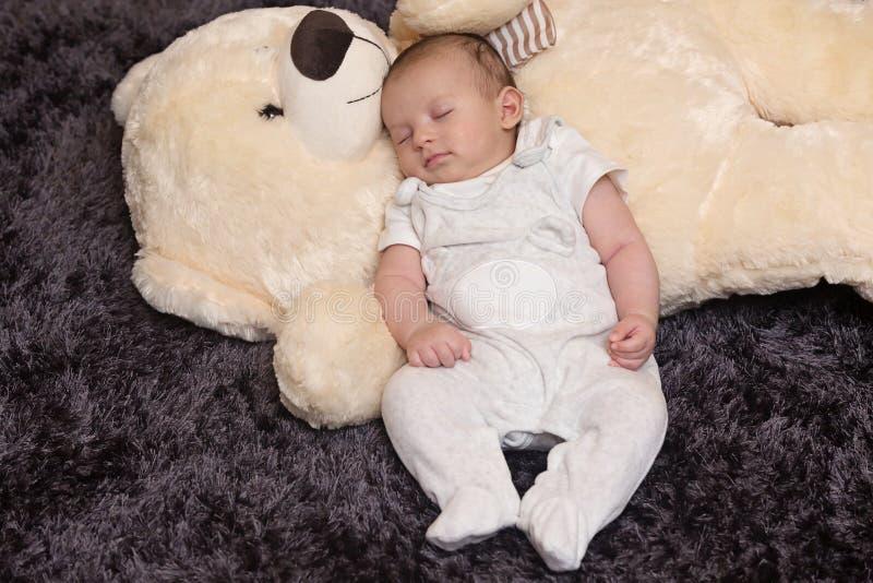 Bebé que duerme con Teddy Bear grande imagen de archivo