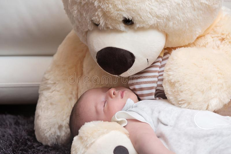 Bebé que duerme con Teddy Bear grande foto de archivo