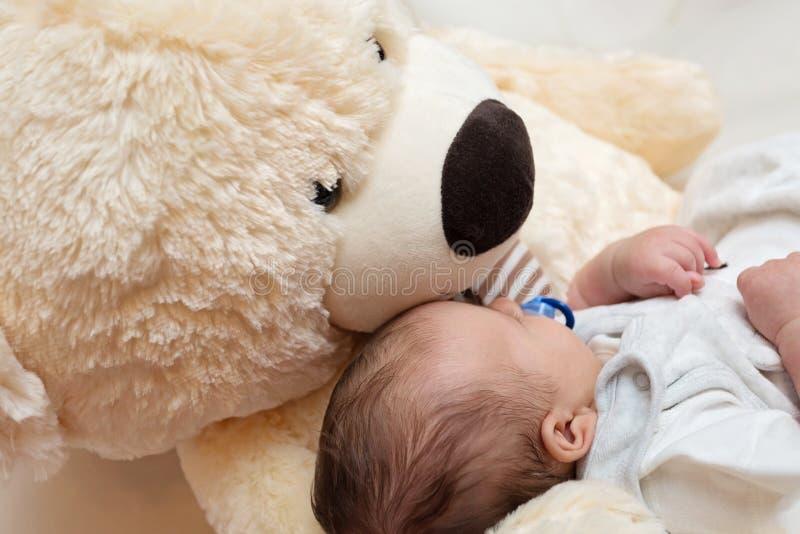 Bebé que duerme con Teddy Bear grande imagen de archivo libre de regalías
