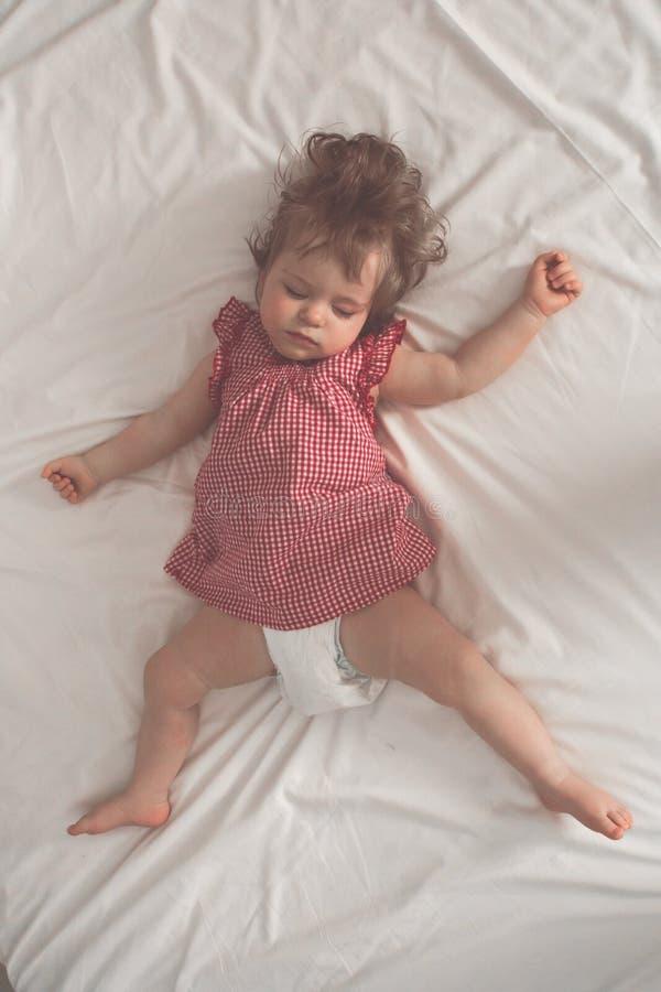 Bebé que duerme en la parte posterior con los brazos abiertos y sin el pacificador en una cama con las hojas blancas El dormir pa imagen de archivo