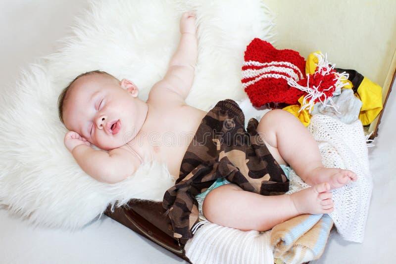 Bebé que duerme en maleta con ropa fotografía de archivo libre de regalías