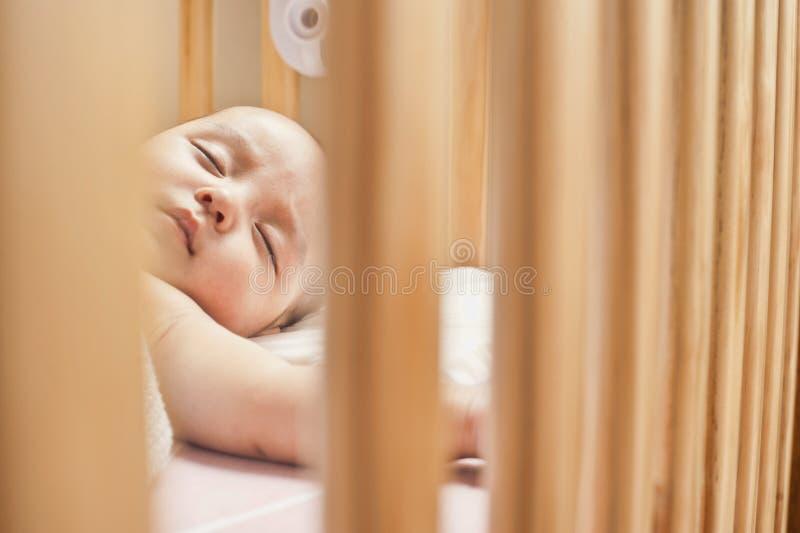 Bebé que duerme en un pesebre imagenes de archivo
