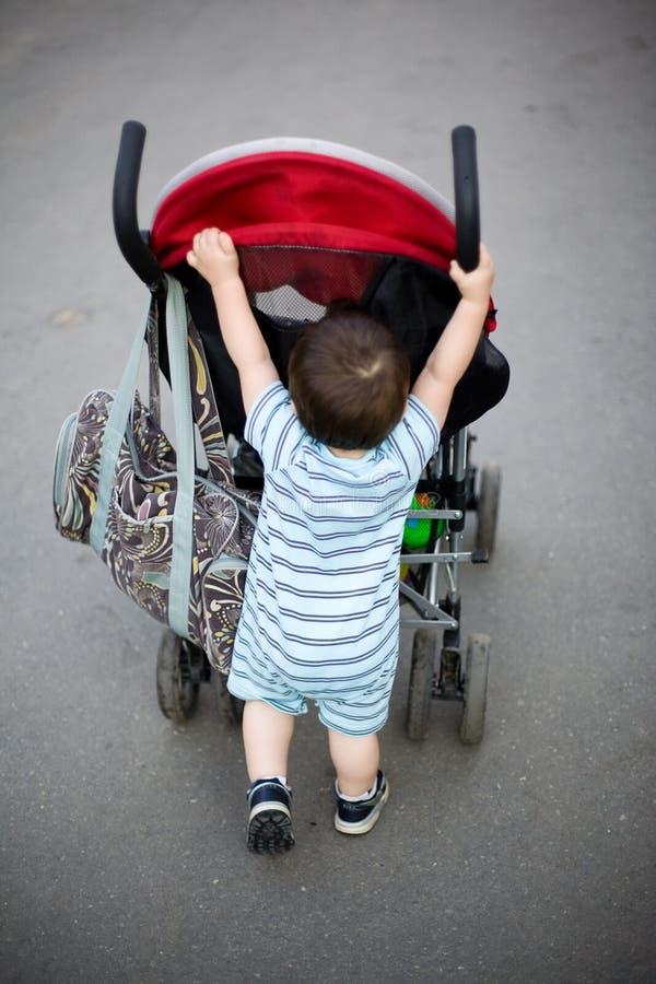 Bebé que empuja el cochecito imagenes de archivo