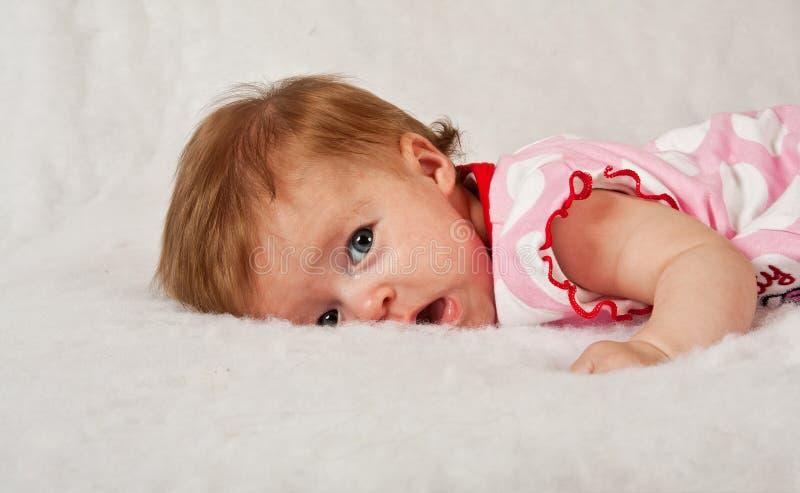 Bebé que encontra-se na superfície macia macia fotografia de stock royalty free