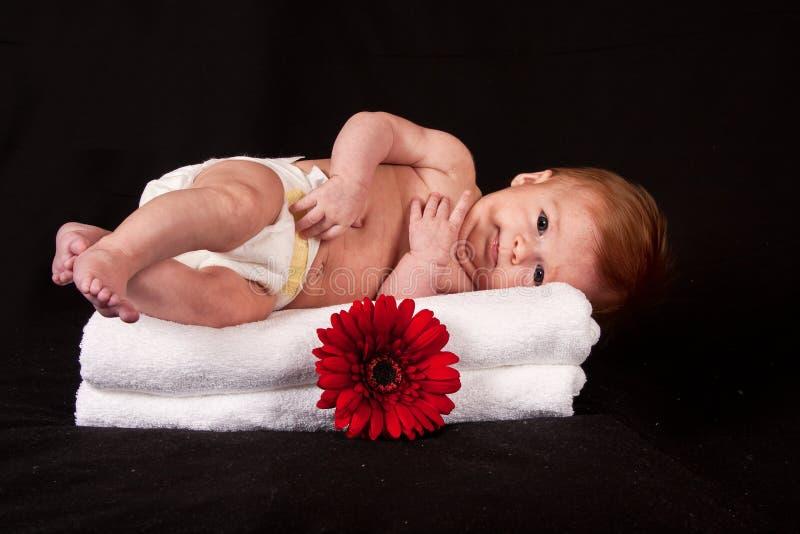 Bebé que encontra-se nas toalhas brancas foto de stock royalty free