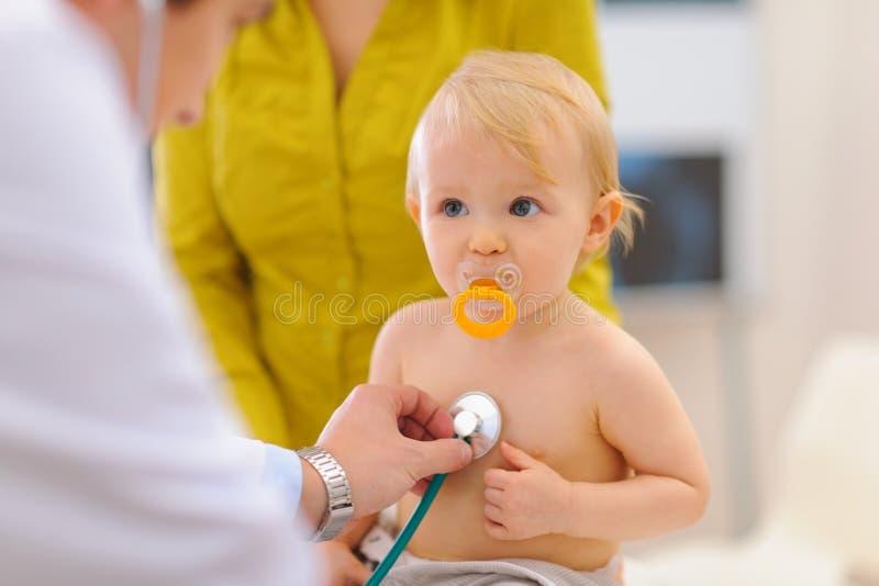 Bebé que es controlado por el doctor que usa el estetoscopio fotografía de archivo