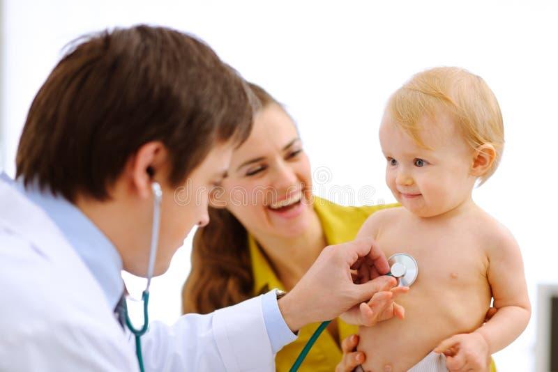 Bebé que es controlado por el doctor que usa un estetoscopio foto de archivo