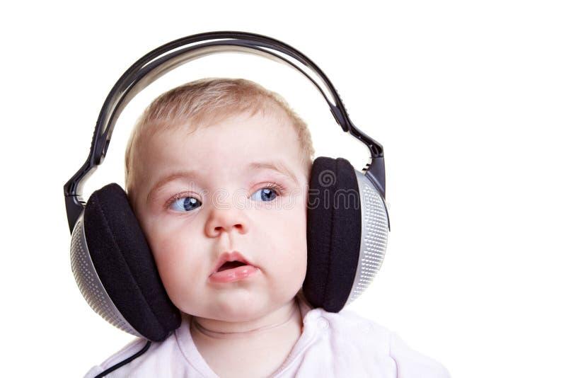 Bebé que escucha la música foto de archivo