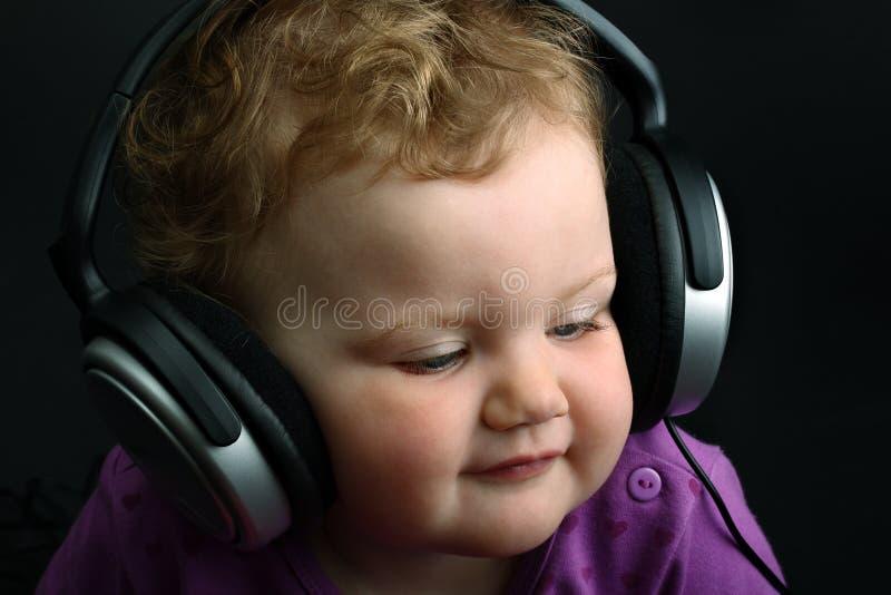 Bebé que escucha la música con los auriculares enormes foto de archivo