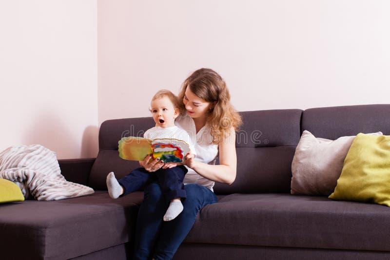 Bebé que escucha su lectura de la madre fotos de archivo
