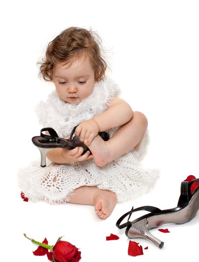 Bebé que intenta en los zapatos de la mama, aislados fotografía de archivo
