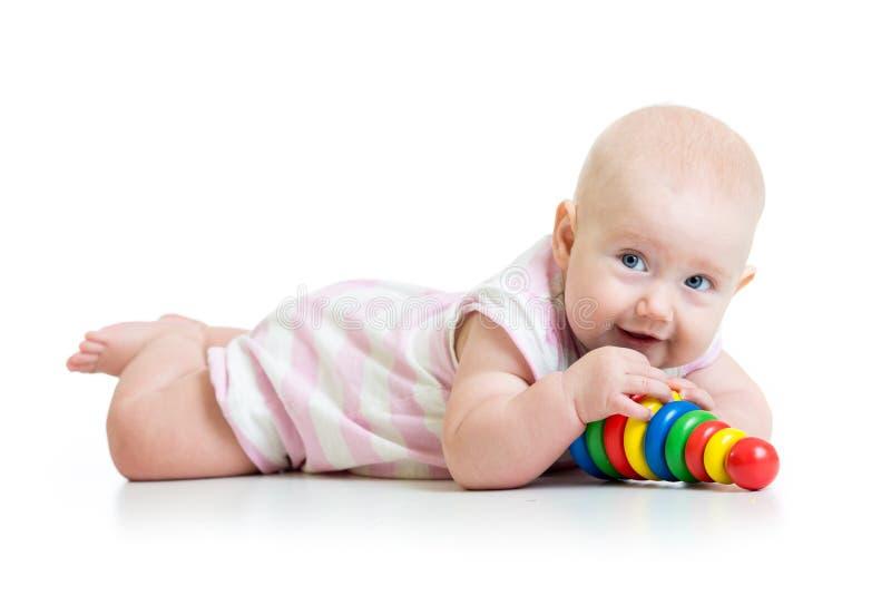 Bebé que juega con el juguete, aislado en blanco imagenes de archivo