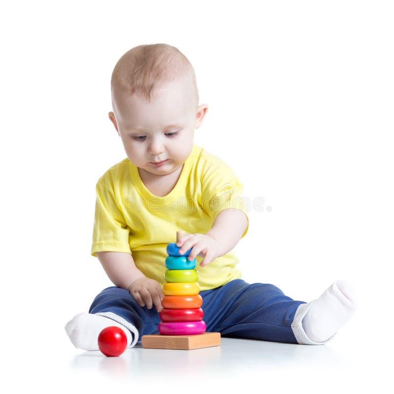 Bebé que juega con el juguete, aislado en blanco foto de archivo