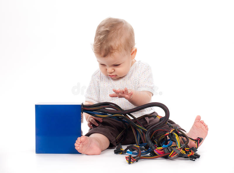 Bebé que juega con la fuente de alimentación de la PC en blanco imágenes de archivo libres de regalías