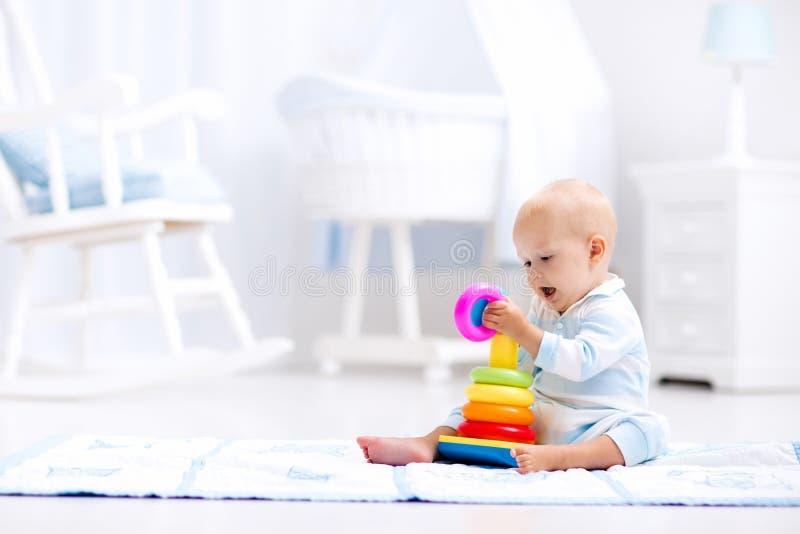 Bebé que juega con la pirámide del juguete Juego de los niños imágenes de archivo libres de regalías
