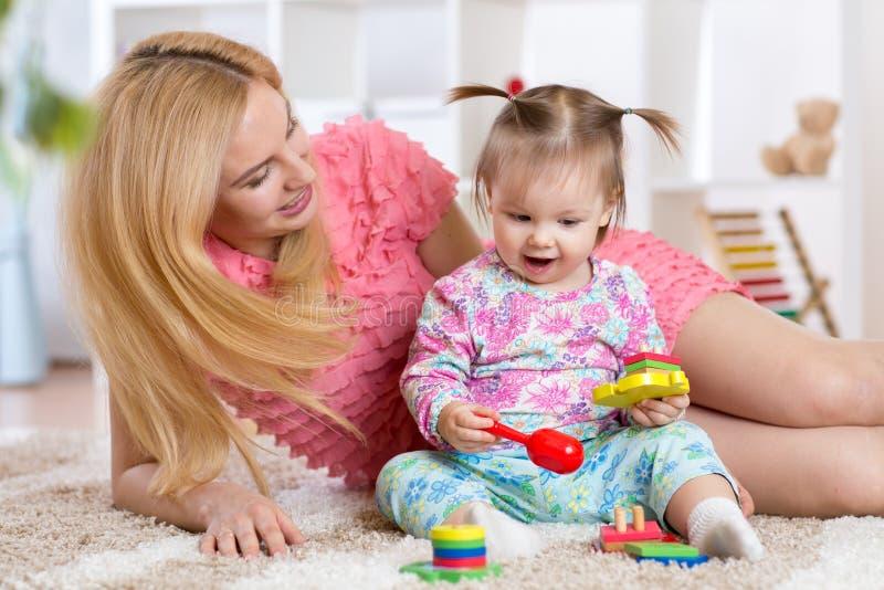 Bebé que juega con su madre en la alfombra en cuarto de niños imagenes de archivo