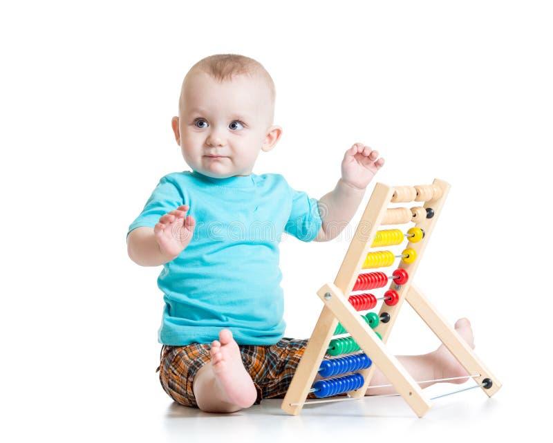 Bebé que juega con un ábaco colorido imagenes de archivo