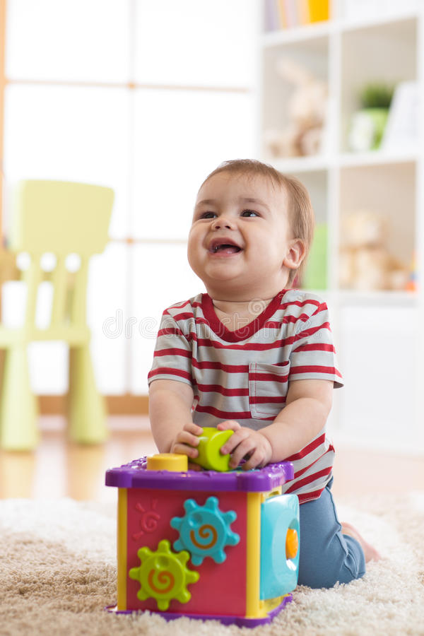Bebé que juega dentro con el juguete del clasificador que se sienta en la alfombra suave fotos de archivo