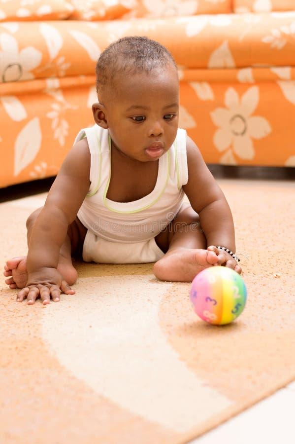Bebé que juega en la casa con una bola imagen de archivo