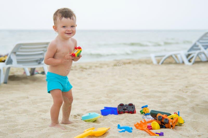 Bebé que juega en la playa arenosa cerca del mar fotos de archivo