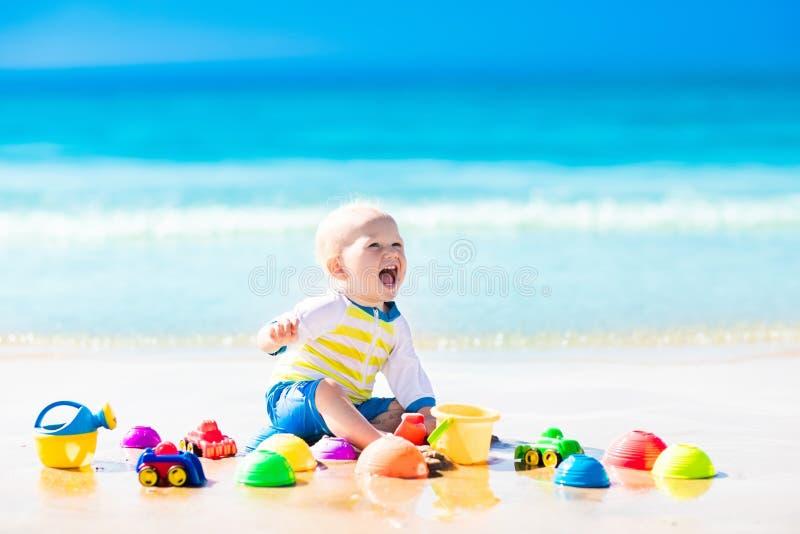 Bebé que juega en la playa tropical que cava en arena fotos de archivo libres de regalías