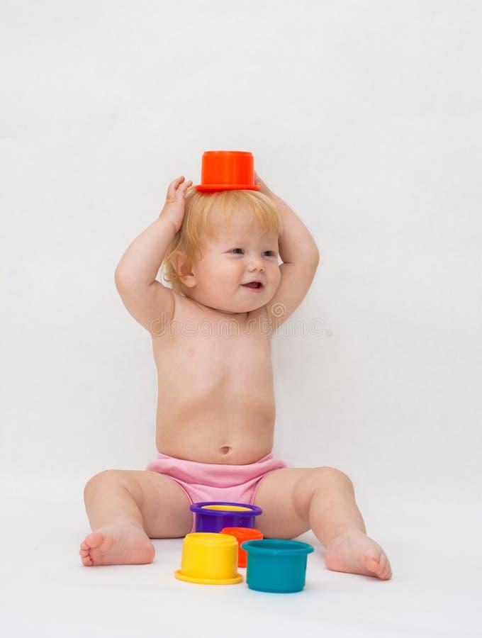 Bebé que juega los casquillos coloridos fotografía de archivo libre de regalías