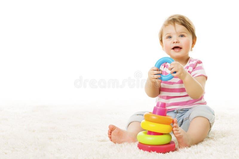 Bebé que juega a Toy Rings, niño infantil con la pirámide colorida foto de archivo
