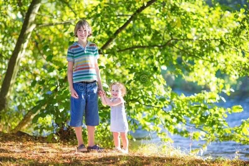 Bebé que lleva a cabo las manos con su hermano en la orilla del río foto de archivo