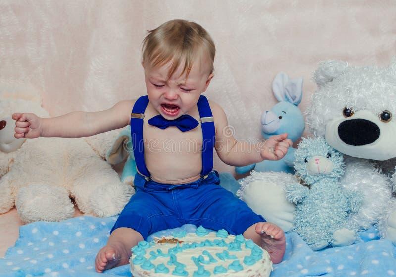 Bebé que llora mientras que come su torta de la fiesta de cumpleaños fotografía de archivo