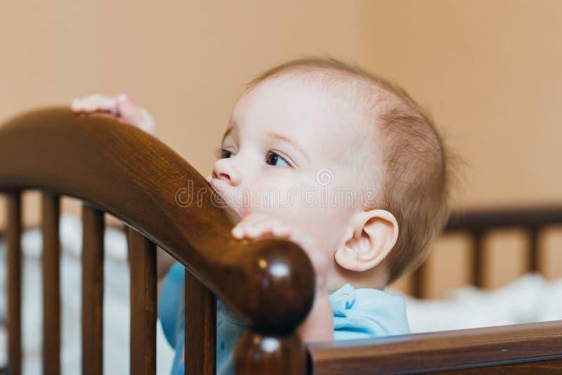 Bebé que mastica en la barra transversal de su pesebre fotos de archivo libres de regalías