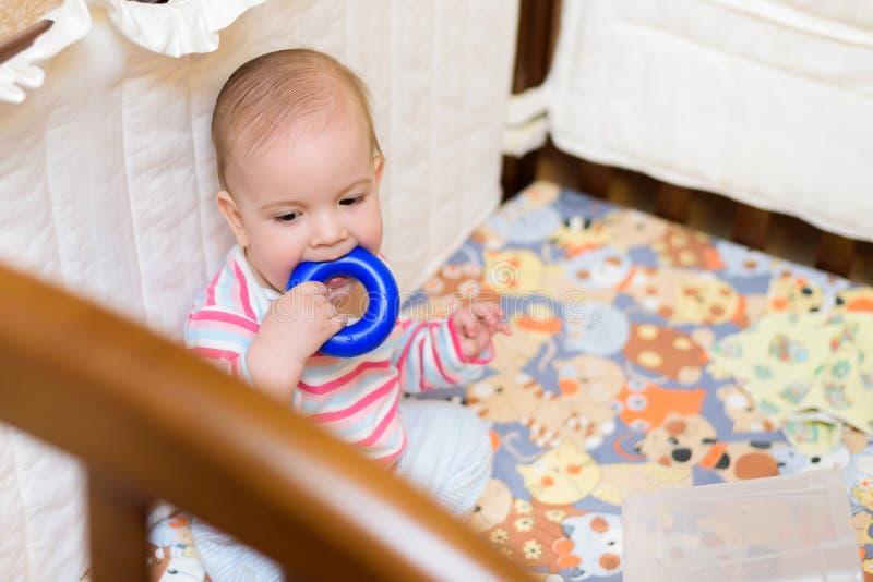 Bebé que mastica un juguete en el pesebre fotografía de archivo libre de regalías