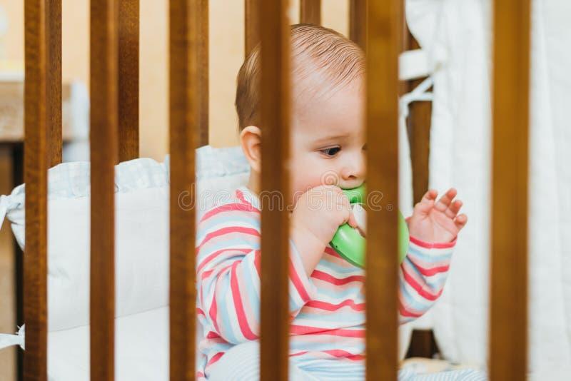 Bebé que mastica un juguete en el pesebre foto de archivo libre de regalías