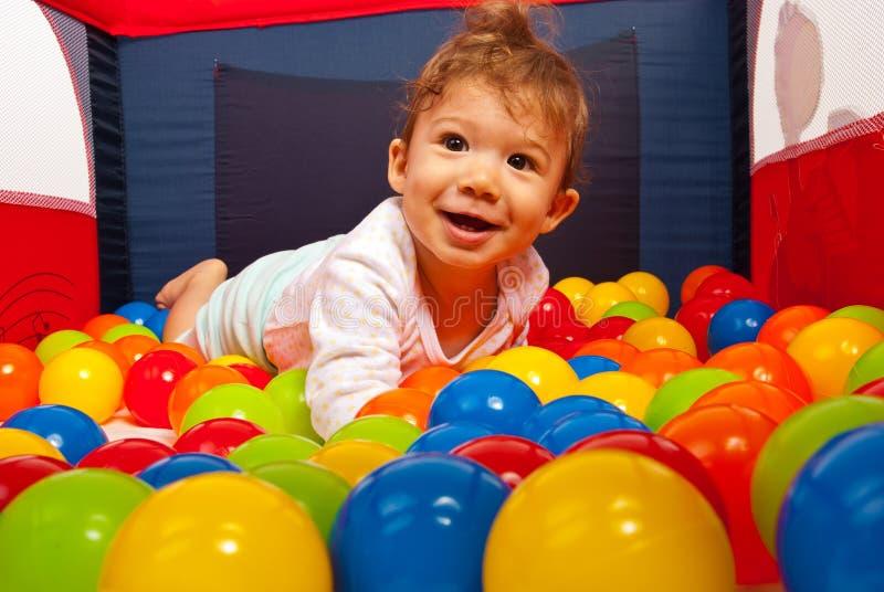 Bebé que miente en bolas coloridas imágenes de archivo libres de regalías